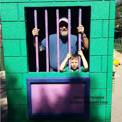 Jimmy standing looking through and holding the bars of a fake jail with grandson Benjamin doing likewise.