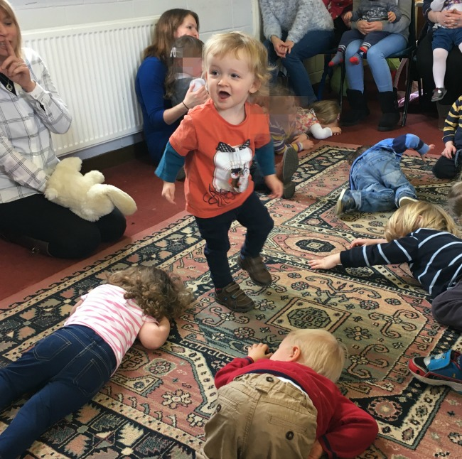 Toddlers laying down and one standing up singing