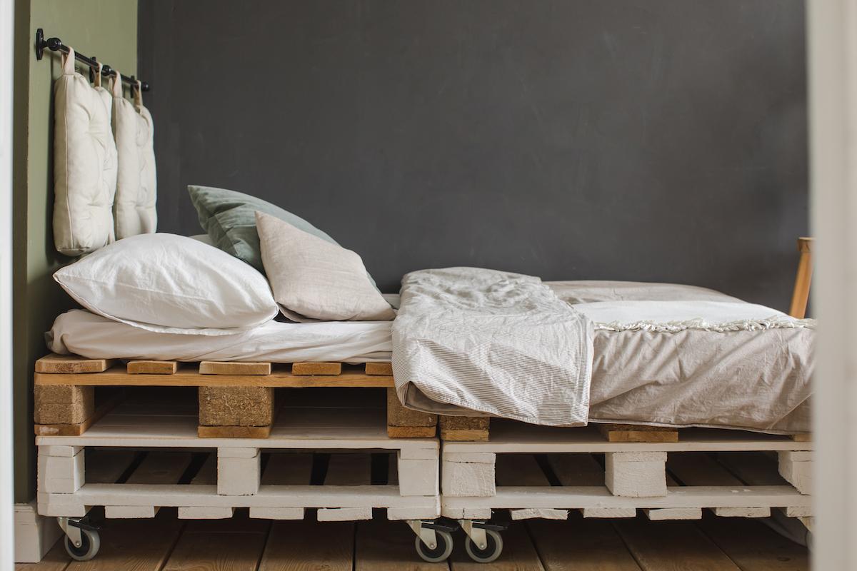 Cama adosada a la pared con somier hecho con palets y ruedas y como cabecero un riel y dos cojines
