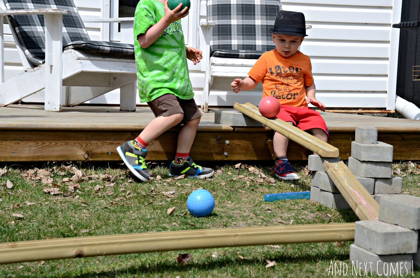 J & K playing with DIY outdoor ball run made from loose parts in the backyard from And Next Comes L