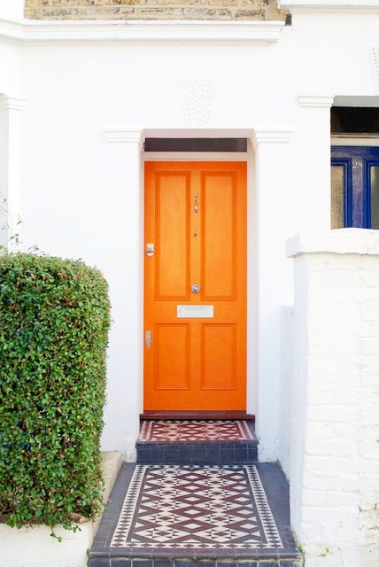 exterior of a white house with an orange door and tiled floor leading up to it