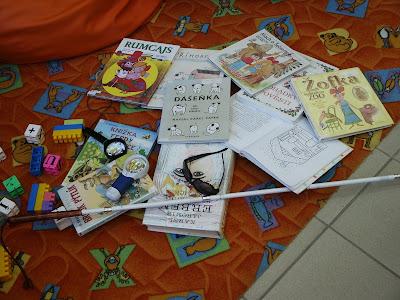 Na koberci leží hromada knih, lupa, tmavé brýle a bílá hůl. Vlevo vedle knih je poházeno několik kostek ze stavebnice