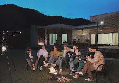 BTS siedzący na zewnątrz nocą przy ognisku przed domem