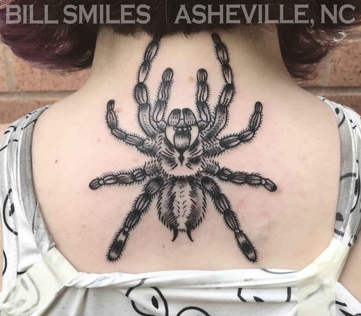 Vemos una joven con un tatuaje de tarántula en la espalda