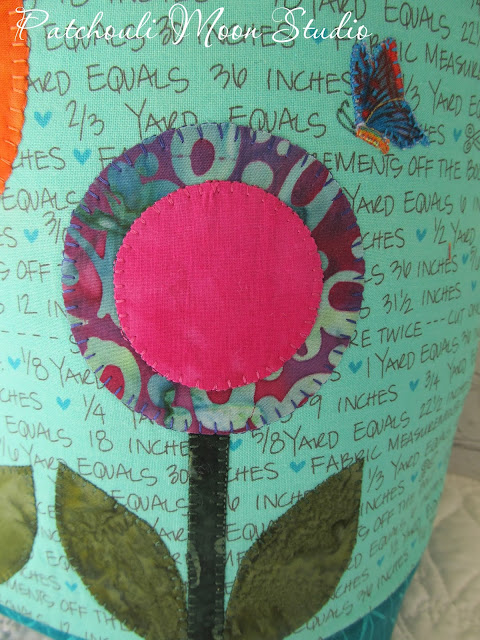 Closeup view of another circle applique flower and applique butterfly on fabric container