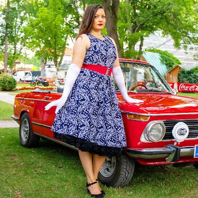christina palfy in einem kleid von boutique new vintage an einem roten oldtimer lehnend bei rocknroll im kurpark Bad Sauerbrunn