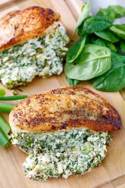 two golden chicken breasts stuffed full of creamy spinach and feta mixture with extra spinach leaves nearby