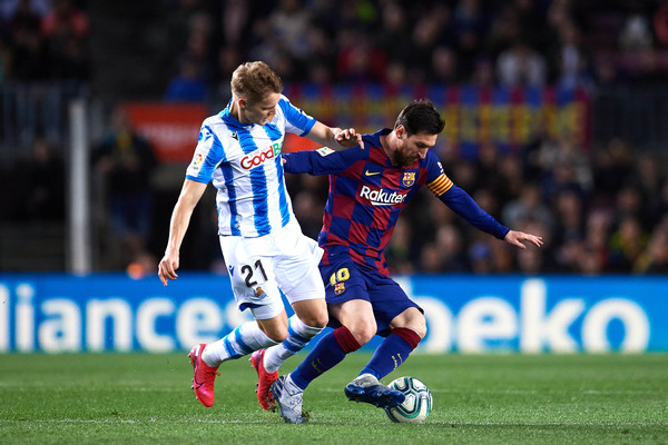 Lionel Messi of FC Barcelona battles for possession with Martin Odegaard of Real Sociedad during the Liga match between FC Barcelona and Real Sociedad at Camp Nou on March 07, 2020 in Barcelona, Spain