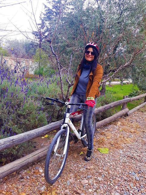 mulher andando de bicicleta em meio a uma paisagem de outono