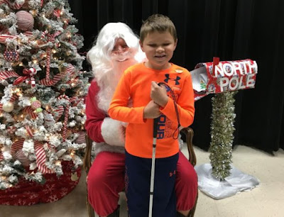 A young boy with a white cane sits on Santa's lap.