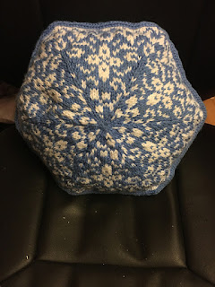 A hexagonal pillow with a floral pattern in white on a blue background. It has a blue rounded edging.