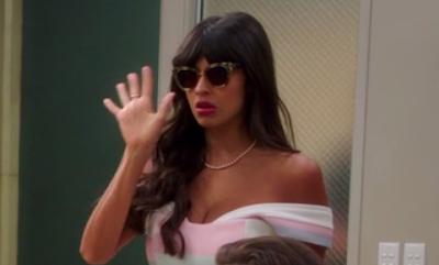 Tahani, wearing sweet tortoiseshell sunglasses, pearls, and an off-the-shoulder pink and blue dress, holding up one hand in a defensive gesture