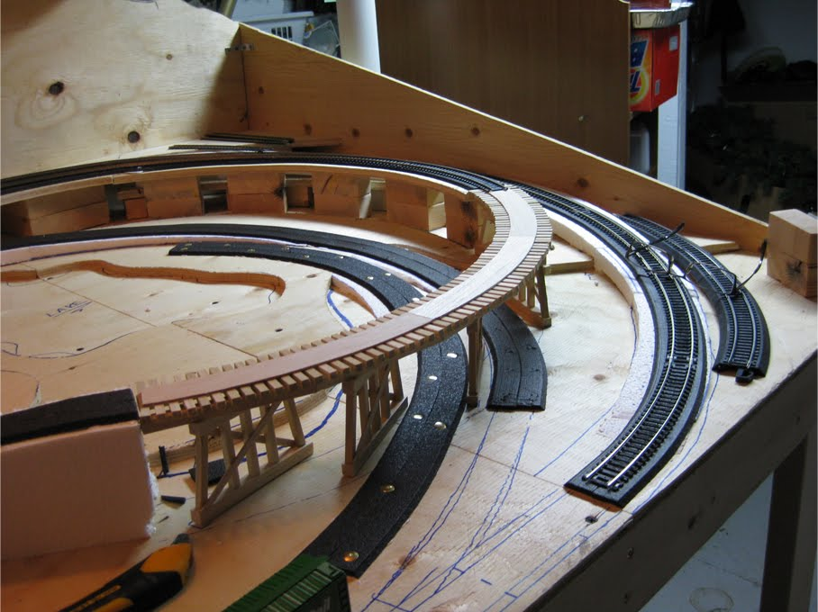 An unpainted wooden train trestle made of wooden dowels and basswood set on the benchwork