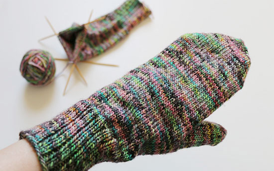 A hand wearing a completed colorful hand knit mitten in the foreground, in front of a mitten in progress on bamboo double point knitting needles next to a ball of wool yarn on a white background.