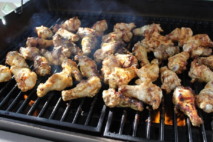 Grilled wings on the grilling grate cooking over a hot fired grilled with seasoning after marinated