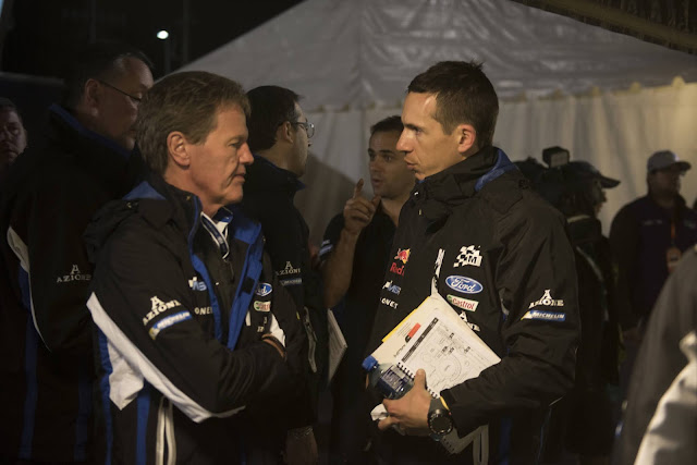 Co-driver Julien Ingrassia talking to M-Sport's Malcolm Wilson