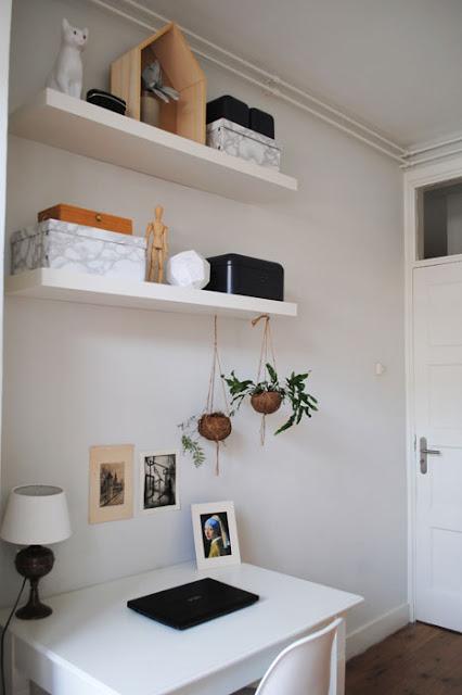 Serene werkplek met marmer look opbergdozen op planken boven een wit bureau.