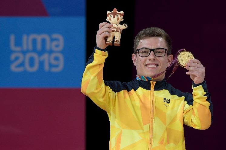 Vitor Tavares sorri para foto enquanto ergue medalha