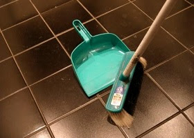 Cleaning a tiled floor with a broom and dust collector.