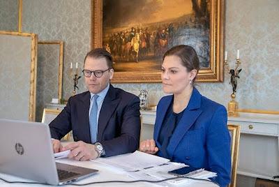 Kronprinsessparet vid skrivbord framför en uppfälld dator.
