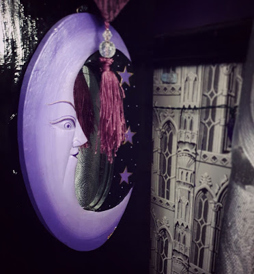 An oval mirror is on the right flank of a black-gloss book-case. The mirror frame depicts a lavender-coloured crescent 'man-in-the-moon' design with a black section with three stars painted on it. It matches the circular mirrors depicted in the picture above. There is a berry-purple tassel hanging partly over it from the altar cloth above, adorned with two clear crystal-effect beads. To the right of the image, the wall behind the book-case is visible, and a little of some greyscale wall-paper depciting Gothic architecture, it is a reproduction of an 1830's design and is in a block-print style.
