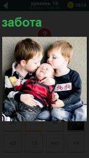 Двое мальчиков на руках держат младенца, осуществляя заботу о нем, который безмятежно спит