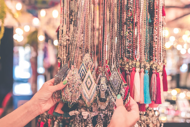 A pair of hands inspecting a bunch of tassels and necklaces at a bazaar.