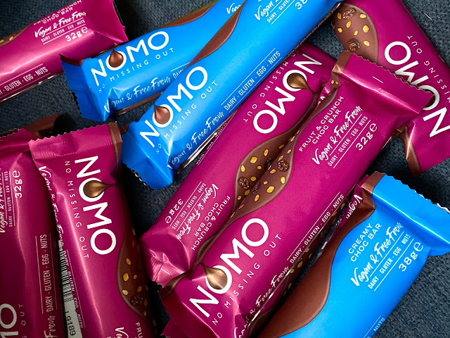 A pile of purple and blue NOMO chocolate bars