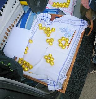 Etwa 30 goldene Schokokugeln auf Tablett. Aufgeteilt in mehrere Fünfer- und Sechsergruppen.