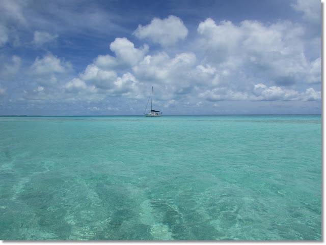 Sailboat anchored on horizon of bright calm turquoise ocean seas.