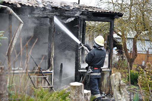 Ugunsdzēsējs ar šļūteni dzēš ugunsgrēku