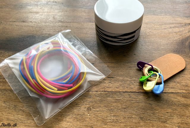 Knit stitch tubes in blue, pink, red and yellow, a cream box and a leather holder for stitch markers