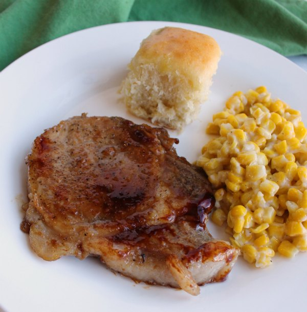close up of braised pork chop with corn and hawaiian roll on dinner plate
