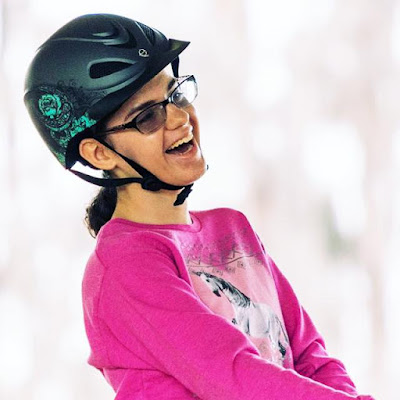 Bryanna is wearing a pink shirt and black riding helmet, laughing and smiling widely