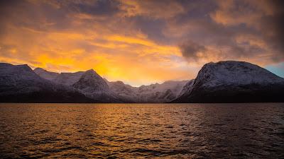 Lago impactante con montañas de nieve de fondo al atardecer