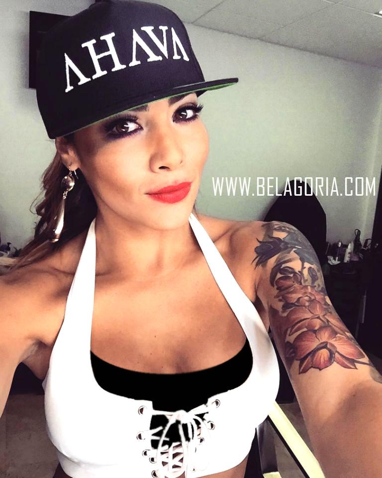 modelo latina con gorra, sujeta la camara mientras se fotografia lleva tatuajes por todos los brazos
