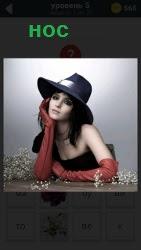 Девушка сидит за столом в шляпке и и перчатками до локтей с большим носом