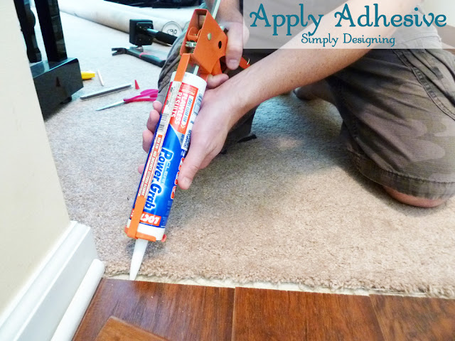 Apply Adhesive for Transition Strip | #diy #carpet #laminateflooring #flooring #homeimprovement | at Simply Designing