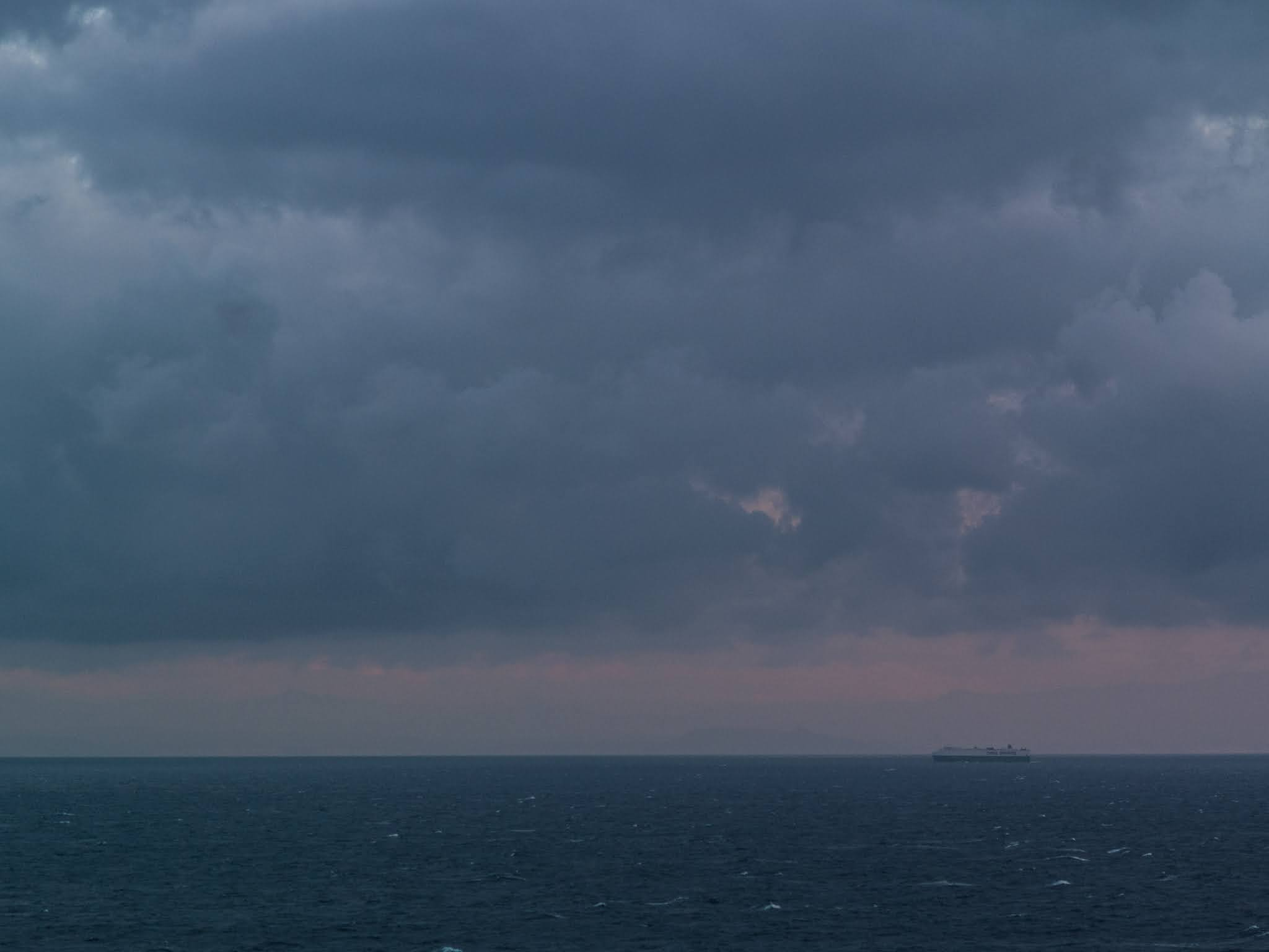 Ship on the horizon at sunset on the Mediterranean Sea.