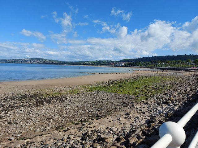 A view across a sand and pebble beach to the shore.  The tide has gone out.
