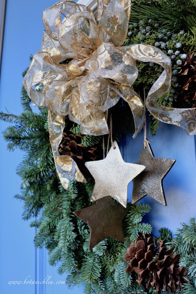 Tips for best ever Christmas wreath on blue front door with gold metal stars and fleur de lis ribbon