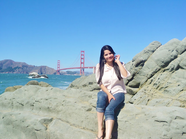 menina de cabelos negros e pele branca com a paisagem de uma praia com agua azul e uma ponte suspensa da cor de ferrugem