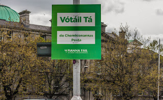 Picture 2: An Irish-only placard in green and white, attached to the pole of a street light on an urban street.