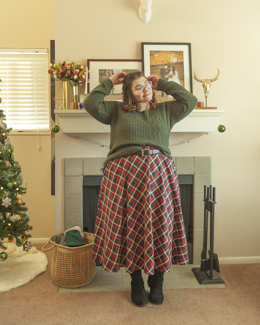 An outfit consisting of a green sweater half tucked into a red, navy blue and white plaid skirt with black ankle boots.