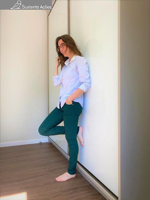 Letícia encostada no guarda-roupa, vestindo calça verde e blusa social listrada