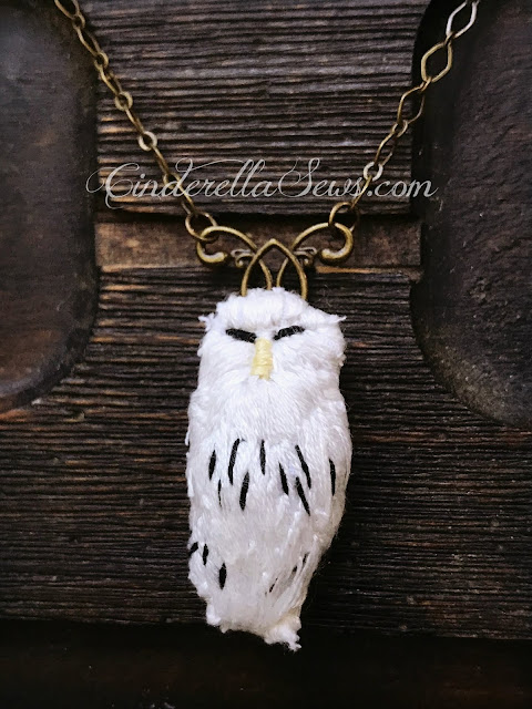 Hedwig Harry Potter Necklace - This handmade pendant was embroidered by hand to look like a tiny snowy owl. He's the perfect companion for a fantasy art and nature lover! The brass chain and folktale style compliments everything from cosplay to office wear Click to learn more about this design and the artist who made it! #hedwig #harrypotter #fanart #handmadejewelry #embroidery #handsewing #textileart #fiberart