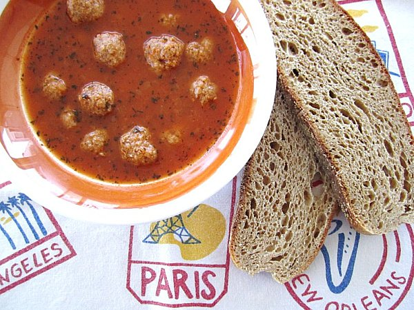 A bowl of Armenian meatball soup with wheat toast next to the bowl