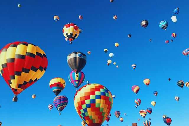colorful hot air balloons rising in the blue sky