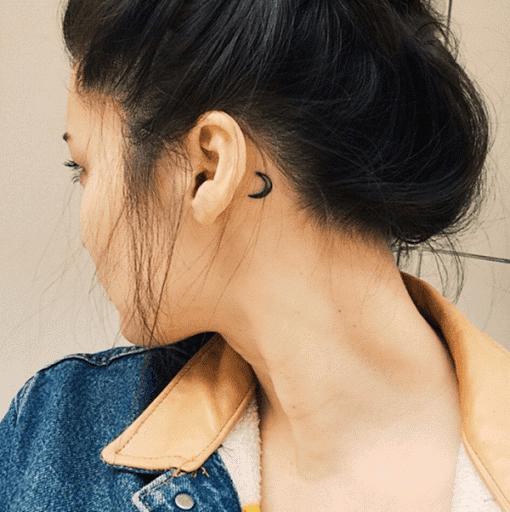 Uma lua crescente é processado por trás do portador da orelha esquerda neste tatuagem.