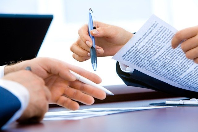 Foto imagem que mostra a assinatura de um contrato onde aparece as mãos de duas pessoas, uma caneta preta e um documento sobre a mesa